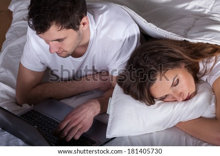 Sleeping wife and her husband using computer