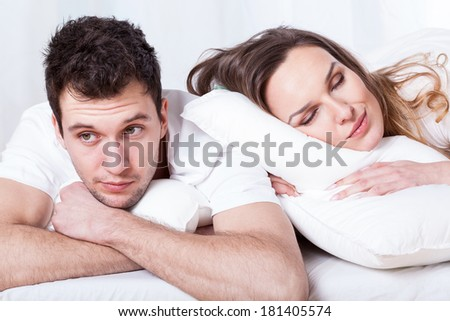 Sleeping wife and thoughtful husband in bed - stock photo