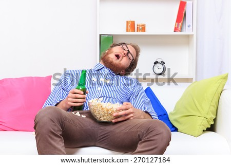 Sleeping with eat in front of TV - - stock photo