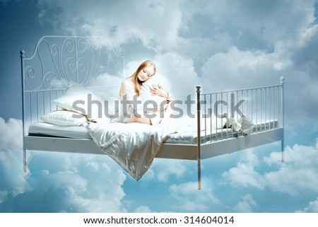 Sleeping woman. Girl with a pillow and blanket on the bed among the clouds in dreams - stock photo
