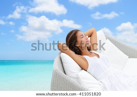 Sleeping woman relaxing lounging on white outdoor sofa day bed lounger on beach ocean background. Asian girl lying down laid back on pillows dreaming or enjoying the sun carefree happy. Home living. - stock photo