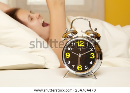 Sleeping woman resting in bed with alarm clock ready to wake her in the morning - stock photo