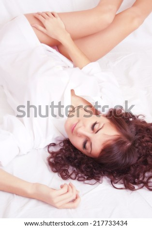 Sleeping young brunette woman on a bad - stock photo