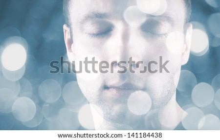 Sleeping young Caucasian man with closed eyes and blurred lights on blue background - stock photo