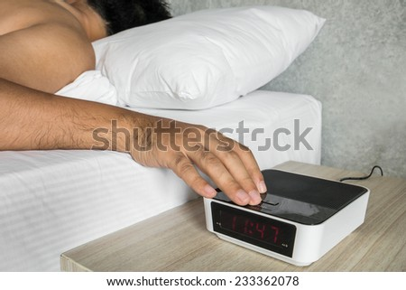 Sleeping young man in bed turning off an alarm clock  - stock photo
