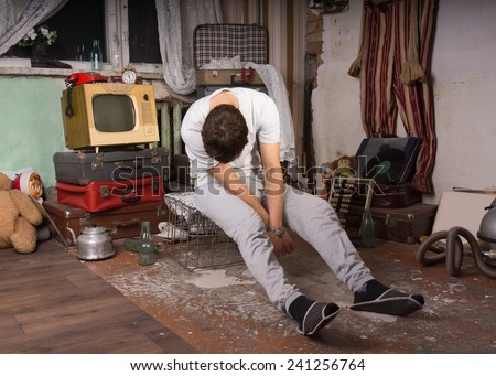 Sleeping Young Man in Casual Clothing Sitting on Cage at Junk Room - stock photo