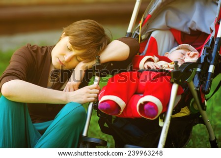 Sleeping young mother and her baby daughter in a stroller - stock photo