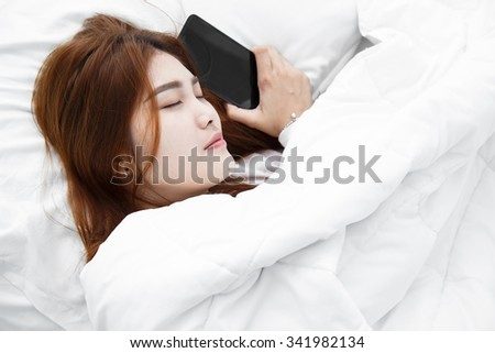 Sleeping young woman lying on bed using her smart phone in her bedroom