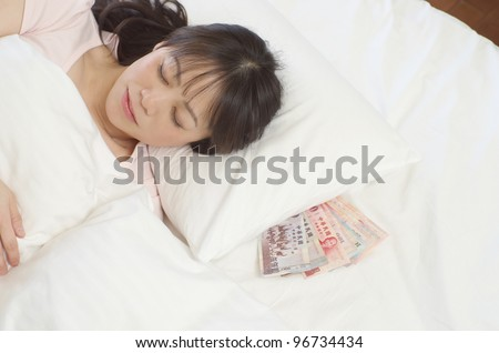 Sleeping young woman with New Taiwan Dollars - stock photo