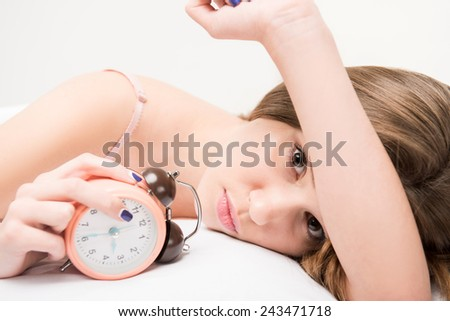 Sleepless beauty. Cropped image of young woman lying in bed and looking at camera failing to fall asleep - stock photo