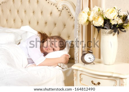 Sleepless woman lying in bed looking at the hours pass by - stock photo
