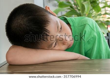 Sleepy Asian boy on table at home. - stock photo