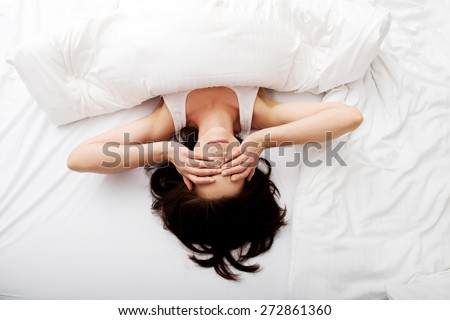 Sleepy brunette woman waking up and rubbing her eyes. - stock photo