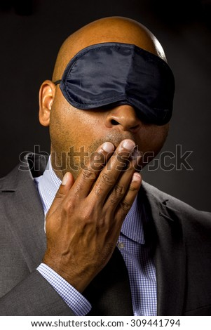 Sleepy businessman wearing an eye mask because of jet lag.  The corporate entrepreneur is sleepy or an insomniac who sleeps during work time.   - stock photo