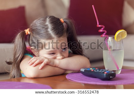 sleepy cute little girl watching tv and having lemonade at home. - stock photo