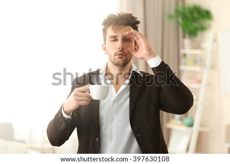 Sleepy guy holding a cup of coffee. - stock photo