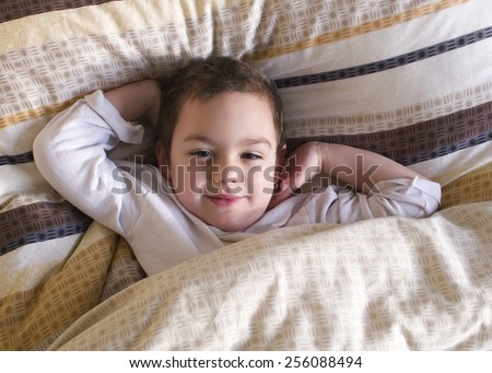 Sleepy happy child lying in a bed, waking up in the morning. - stock photo