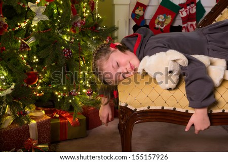 Sleepy little girl on a sofa near the christmas tree
