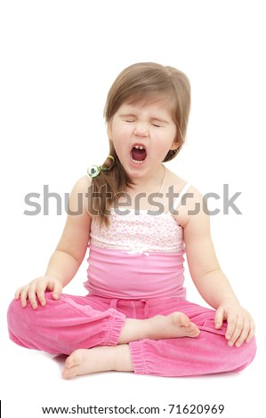 sleepy little girl sits like a turk on white and yawning