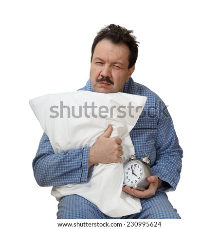 Sleepy male sits hugging pillow and hold an alarm clock in hand isolated on white background. Insomnia concept - stock photo