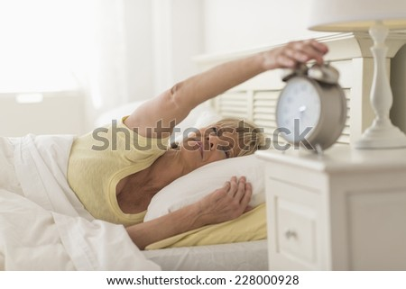 Sleepy mature woman pressing button of alarm clock while lying in bed at home - stock photo