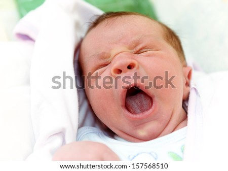 Sleepy New Born Baby Yawning with His Mouth Open - stock photo