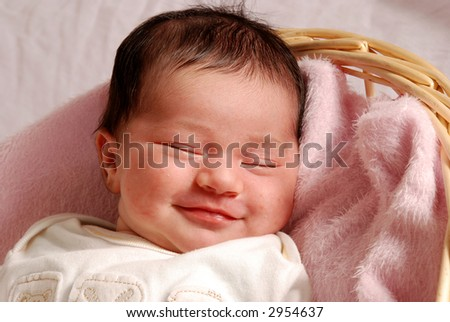 sleepy, smiling baby in basket - stock photo