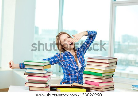 Sleepy student stretching herself after a night of studying - stock photo