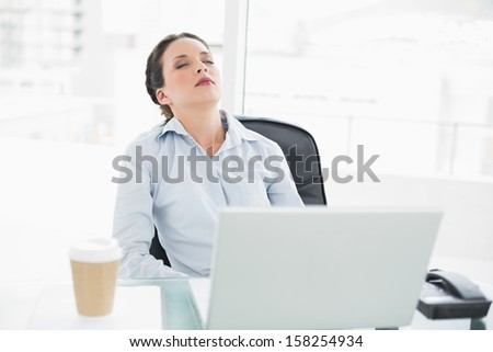 Sleepy stylish brunette businesswoman relaxing at her desk in bright office - stock photo