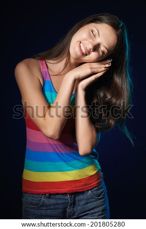 Sleepy woman. Beautiful smiling woman holding palms on her cheek in drowsy state,  over dark background - stock photo