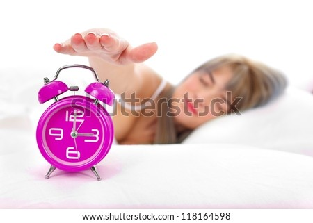 Sleepy woman turning off the alarm clock at home