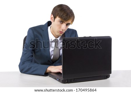 sleepy young caucasian businessman on desk with laptop - stock photo