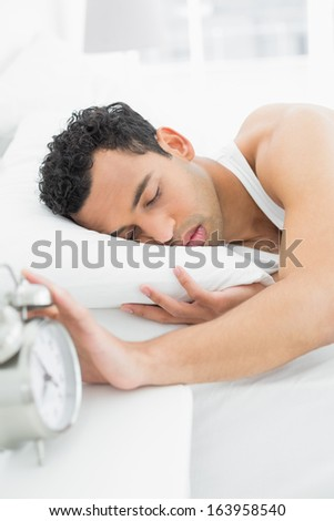 Sleepy young man in bed extending hand to alarm clock - stock photo