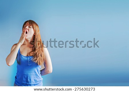 Sleepy young woman is yawning early in the morning background