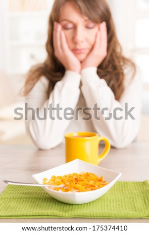 Sleepy young woman trying to eat cornflakes and drink morning coffee - stock photo