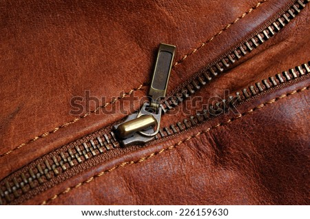 Sleeve zipper detail of a brown leather jacket, showing nylon seams - stock photo