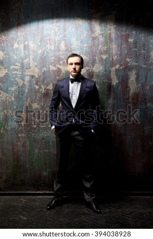 Slender and elegant stylish dressed man standing in the beam of light against the dark colored background - stock photo