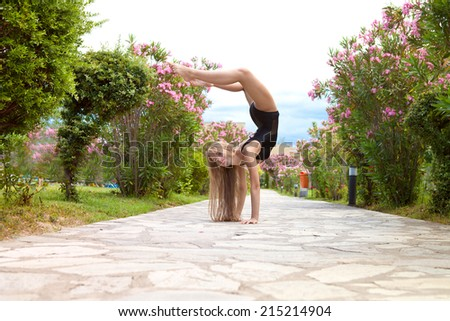 Slender athletic girl doing exercises in nature