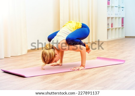 Slender athletic girl doing yoga exercises indoor. Professional trainer.