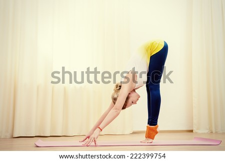 Slender athletic girl doing yoga exercises indoor. Stretching. - stock photo