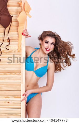 Slender attractive girl chooses a swimsuit in a store. - stock photo
