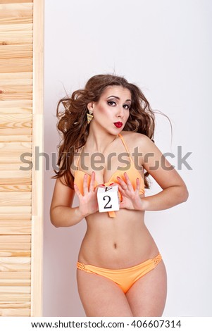 Slender attractive girl in a swimsuit. Girl holding a number two. Shopping. Preparation for the beach season. - stock photo