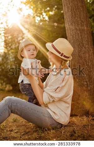 Slender beautiful blonde mom in jeans, a beige shirt and a hat holding a baby boy on the background of the Park at sunset and smiles - stock photo