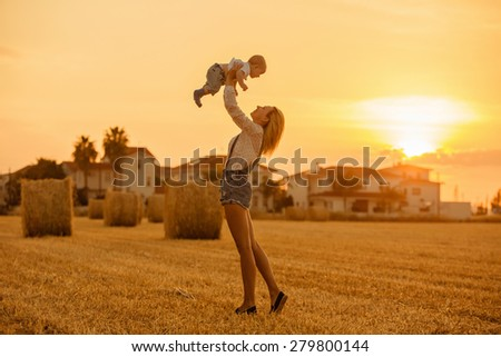 Slender beautiful blonde mom in jeans suit baby throws up in the background of straw fields at sunset and smiles - stock photo