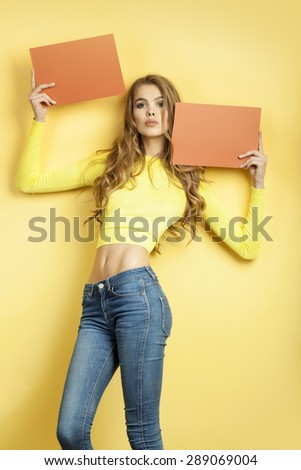 Slender beautiful young woman with long curly hair in yellow blouse and blue jeans holding two orange brown sheets of paper standing on yellow background, vertical picture - stock photo