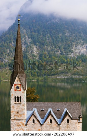 Slender belfry and Lutheran church on the shore of Lake Hallstatt. On the opposite shore of the lake - the beautiful mountains overgrown with forests. Thesmall town in Austria - Hallstatt