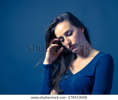 Slender caucasian female with somber or gloomy expression - stock photo