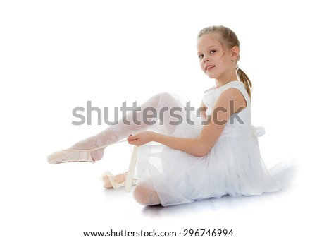 Slender, flexible young blonde girl in a long white silk summer dress sits on the floor and puts on foot in Pointe shoes , girl dancing or ballet.-Isolated on white - stock photo