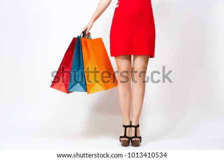 Slender long female legs in black sandals, caucasian woman in red dress holding three multi colored packets with purchases after shopping isolated on white background. Copy space for advertisement