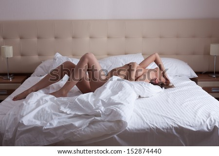 Slender nude woman getting orgasm in bed - stock photo